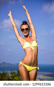 Summer lifestyle image of slim sexy tanned woman with perfect fit sportive body, wearing stylish bikini and sunglasses, put her hands to the air, amazing view on island.