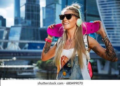 Summer lifestyle image of trendy pretty girl with pink penny board on skyscrapers background. Tattoo model. Smiling and listening music in stylish headphones. Wearing stylish sunglass, denim overalls