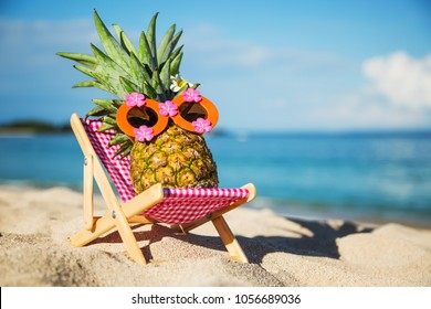 Summer lifestyle image of young pretty girl-pineapple lying on sunbed on the sand against turquoise sea. Wearing funny sunglasses, the flower in the tail. Tropical summer vacation concept. Sunbathing