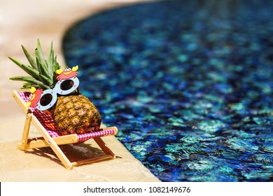 Summer lifestyle image of young pretty girl-pineapple lying on sun chaise near the turquoise swimming pool. Wearing funny sunglasses. Rest in paradise. Tropical summer vacation concept. Sunbathing