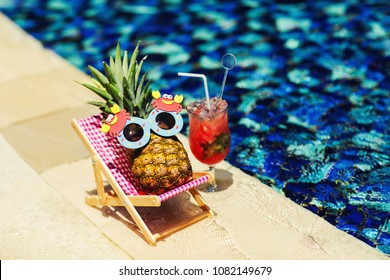 Summer lifestyle image of young pretty girl-pineapple lying on sun chaise near the turquoise swimming pool. Wearing funny sunglasses. Drinking fresh juice. Tropical summer vacation concept. Sunbathing