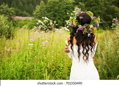 Summer lifestyle portrait of beautiful young brunette woman with perfect long curly hair in a wreath of wild flowers. Standing back in the flower field, hugging herself by the waist. Romantic mood