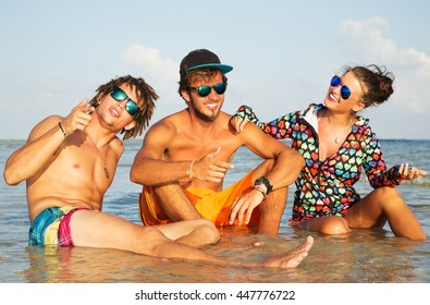 Summer lifestyle portrait of company of young cheerful best friends. Smiling, having fun, sitting on the water and looking each other. Wearing stylish sunglasses and bright t-shirt.  Surf style