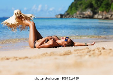 Summer lifestyle portrait of happy pretty young woman with tanned sexy body. Enjoying life and lying on the beach of the tropical island. Stylish wide brimmed straw hat. Leg up. Vacation concept