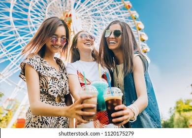 Summer lifestyle portrait multiracial women enjoy nice day, holding glasses of milkshakes. Happy friends inin front of ferris wheel. Best friends girls having fun, joy. Lifestyle. Asian, jewess and