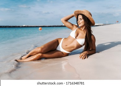 Summer lifestyle. Portrait of pretty girl with slim tanned sexy body in white bikini enjoying life and lying on the sand on the beach of tropical island. Vacation