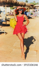 Summer lifestyle portrait of pretty girl walking on the beach of tropical island. Wearing stylish short summer polka-dot dress and straw hat. Holding inflatable yellow beach bag. Tanned fit sexy body.