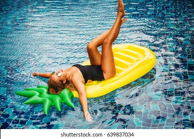 Summer lifestyle portrait of pretty girl having fun on air mattress in the swimming pool. Feet up. Wearing stylish bikini and mirrored sunglasses. Smiling, doing yoga. Positive emotions, bright colors
