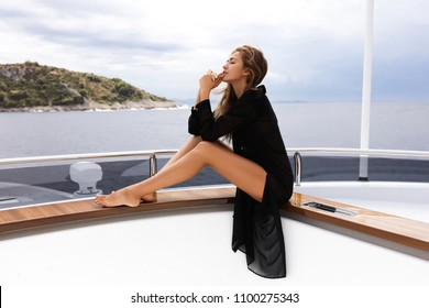 Summer lifestyle portrait of pretty happy young girl with tanned sexy body. pretty face posing on yacht, smiling and sitting, tropical island beach with clear water. Long legs,volume hair,pedicure,spa
