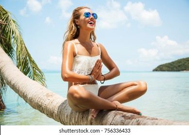 Summer lifestyle portrait of pretty happy young girl with tanned sexy body. Doing yoga, smiling and sitting on palm tree at the tropical island beach with clear water. Wearing stylish bikini, sunglass