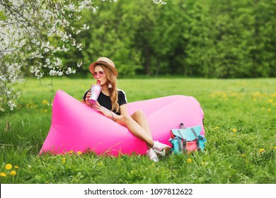 Summer lifestyle portrait of pretty smiling girl sitting on the pink inflatable sofa in the blooming park. Wearing stylish sunglasses, canotier hat. Relaxing, enjoying life on air bed. Inflatable Sofa