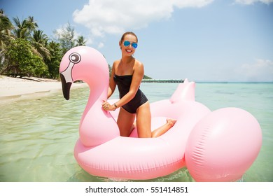 Summer lifestyle portrait of pretty smiling girl swimming on air mattress in the ocean, wearing black bikini and mirrored sunglasses. Smiling and having  fun. Positive emotions, bright colors