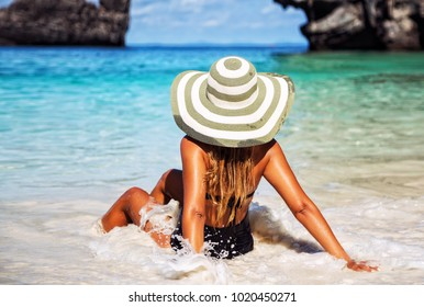 Summer lifestyle portrait of pretty young suntanned woman. Enjoying life and sitting on the beach of the tropical island. Wearing stylish bikini and wide brimmed hat with stripes. Looking at the sea