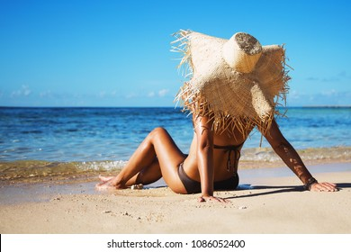 Summer lifestyle portrait of pretty young suntanned woman. Enjoying life and sitting on the beach of the tropical island. Wearing stylish bikini and wide brimmed straw hat. Looking at the sea. Sunny