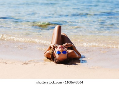 Summer lifestyle portrait of pretty young girl with tanned sexy body. Enjoying life and lying in the clear sea water on the beach of the tropical island. Wearing stylish gold bikini and sunglasses.