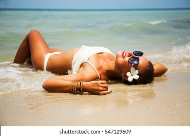 Summer lifestyle portrait of pretty young girl with tanned sexy body. Enjoying life, smiling and lying in the clear sea water on the beach of the tropical island . Wearing white bikini and sunglasses