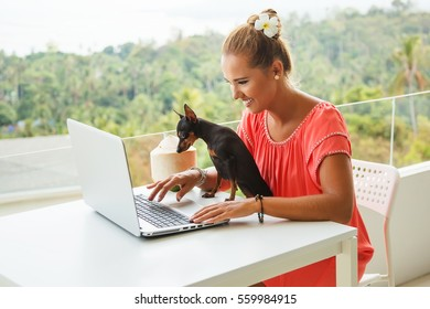 Summer lifestyle portrait of pretty young girl working at the laptop in the balcony of resort of the tropical island. Cute small dog helping to work. Wearing stylish coral color dress. Freelance