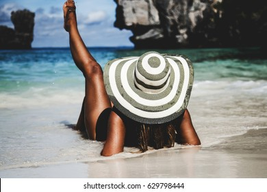 Summer lifestyle portrait of pretty young woman with tanned sexy body. Enjoying life and lying in the clear sea water on the beach of the tropical island. Wearing stylish wide brimmed hat. Leg up