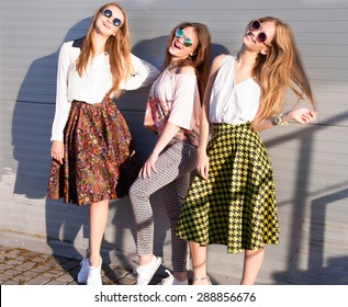 Summer lifestyle portrait of tree pretty young woman friends having fun together,nice summer day at vintage colors,three hipster girls enjoy their vacation,ready for party.shopping girls,party people