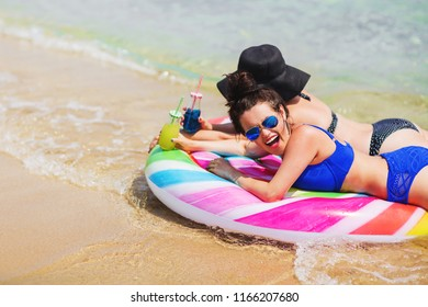 Summer lifestyle portrait of two pretty girls friends having fun on air mattress in the clear sea water. Wearing stylish bikini and mirrored sunglasses. Smiling, drinking lemonade. Positive emotions