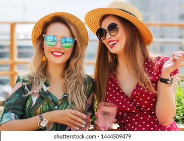 Summer lifestyle portrait of two pretty girls friends sitting on the roof terrace with two glasses of champagne. Smiling and having fun. Wearing stylish summer dresses, straw hats, sunglasses. Joyful