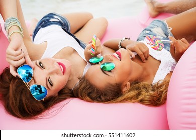 Summer lifestyle portrait of two pretty girls friends on the beach with yummy lollipops, wearing white t-shirts, short denim shorts and mirrored sunglasses. Smiling and having  fun. Positive emotions