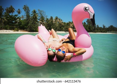 Summer lifestyle portrait of two pretty girls friends having fun on air mattress in the ocean. Wearing stylish bikini and mirrored sunglasses. Smiling and hugging. Positive emotions, bright colors