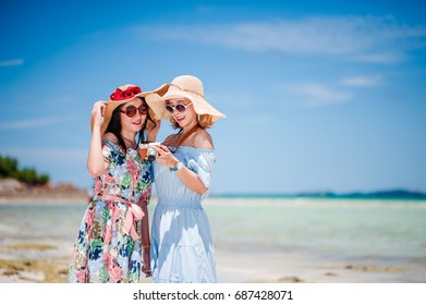 Summer lifestyle portrait of two pretty best girls friends on the beach.. Wearing dress and sunglasses. Smiling and relaxing.View image from the camera.