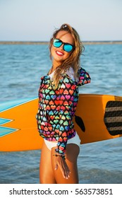Summer lifestyle portrait of young pretty girl with sportive tanned body, posing with the surf board on the beach. Wearing bright t-shirt and stylish sunglasses. Ready for surfing