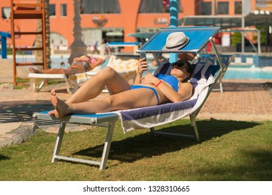 Summer lifestyle portrait of young stunning woman lying on the sunbed on the beach of the tropical island and uses smartphone. Young white woman lying on blue sunbed