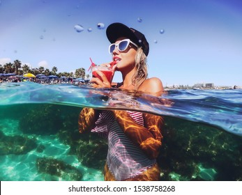Summer lifestyle portrait of young stunning blonde girl. Enjoying life, smiling, drinking cocktail in the turquoise sea. Wearing stylish sunglasses, stripes swimsuit. Half over half under water.