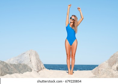 Summer lifestyle. Sexy tanned woman in blue one-piece swimsuit on the tropic beach