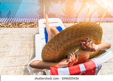 Summer lifestyle traveler woman in bikini and big hat joy relaxing sunbathe on luxury swimming pool in resort near the beach, Holiday summer outdoor vacation and travel trip