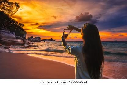 Summer lifestyle traveler woman hand doing finger frame joyful scenery sea beach landscape at sunset Similan island, Enjoy famous travel Phuket Thailand holiday vacation trip, Tourism destination Asia