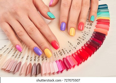 Summer manicure and nail color samples. Young woman hands with multicolored manicure and collection of color nail polish samples. Nail beauty salon.