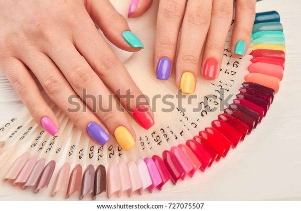 夏のマニキュアとネイルカラーのサンプル。多彩色のマニキュアを持つ若い女性の手と、カラーのマニキュアサンプルのコレクション。ネイル美容サロン。