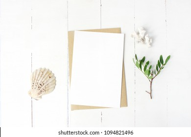 Summer marine stationery, desktop mock-up scene. Blank greeting card, craft envelope, seashell, coral and lentisk branch. Old white wooden table background. Flat lay, top view.