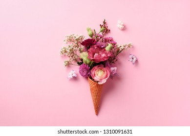 Summer minimal concept. Ice cream cone with pink flowers and leaves on punchy pastel background. Flat lay. Top view. Creative layout.