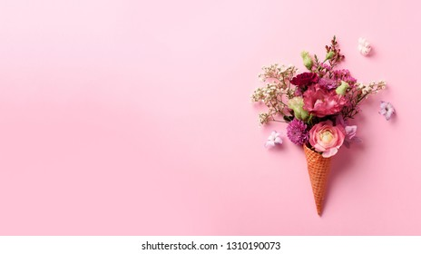 Summer minimal concept. Ice cream cone with pink flowers and leaves on punchy pastel background. Flat lay. Top view. Banner. Creative layout.