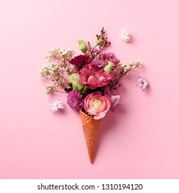 Summer minimal concept. Ice cream cone with pink flowers and leaves on punchy pastel background. Flat lay. Top view. Creative layout. Square crop.