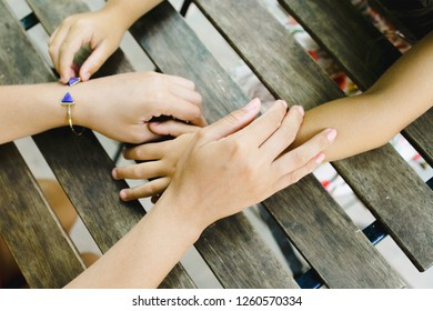 Summer mood, family portrait, sistership concept. Young woman and little girl hold their hands crossed on a wooden table