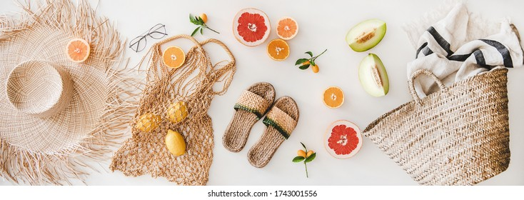 Summer mood layout. Flat-lay of summer natural sandals, straw sunhat, beach rafia and net bag, striped beach towel, sunglasses and cut fresh fruits over white plain background, top view