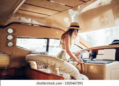 summer mood photo Beautiful blonde woman model in a hat and dress inside a yacht at the wheel