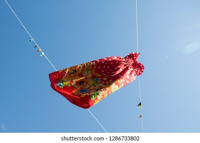 summer mood, a red sundress is dried on a rope against a blue sky