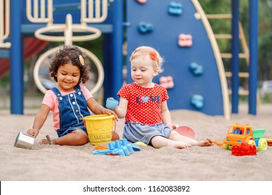 Summer mood. Two cute Caucasian and hispanic latin babies children sitting in sandbox playing with plastic colorful toys. Little girls friends having fun together on playground.