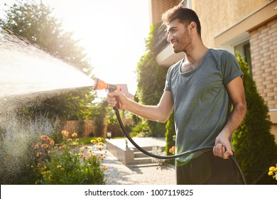 Summer morning in countryside house. Portrait of young attractive tan-skinned bearded man in blue t-shirt smiling, watering plants with hose, working in garden.
