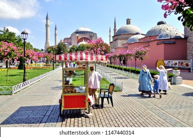 Summer Morning in Istanbul's Old City: Family Walking by Simit Salesman and Traditional Red Cart in Sultan Ahmet Park, with a view of Istanbul's Famous Hagia Sophia - Istanbul, Turkey