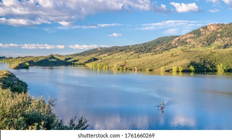 summer morning on  Horsetooth Reservoir at foothills of Rocky Mountains in northern Colorado with a stand up paddler, popular recreation destination in Fort Collins area