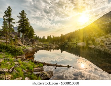 Summer morning over little lake. Sun rays shine between clouds. Ergaki Nature Park. Krasnoyarsk region Russia