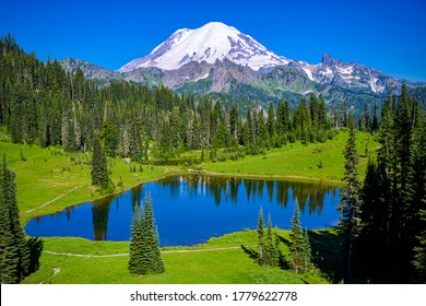 Summer mountain green valley lake and peak snow. Mountain lake landscape. Mountain gree valley lake view. Lake at mountain peak snow